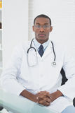 Serious male doctor sitting at medical office Stock Images