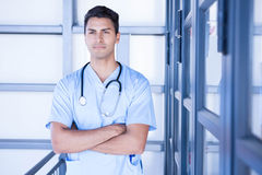 Serious male doctor standing with arms crossed. In hospital Royalty Free Stock Photos