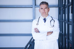 Serious male doctor standing with arms crossed. Portrait of serious male doctor standing with arms crossed in hospital Stock Photo