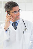 Serious male doctor using mobile phone Royalty Free Stock Images