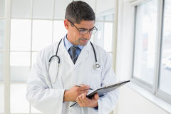 Serious male doctor writing reports Stock Images