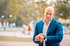 Serious male entrepreneur in formal suit looking at wristwatch planning working schedule , confident executive manager checking ti. Serious male bald Stock Image