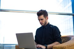 Serious male entrepreneur working on web page via notebook. Boss online booking stock photo