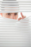 Serious male eyes spying through roller blind Royalty Free Stock Image