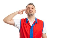 Hypermarket employee touching temple with hand as military concept. Serious male hypermarket or supermarket employee wearing red and blue vest touching temple stock image