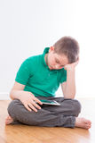 Serious Male Kid Reading at his tablet Computer Royalty Free Stock Image