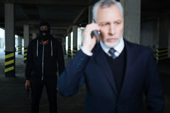 Serious male kidnapper wearing a mask. Dangerous criminal. Serious dangerous male kidnapper wearing a mask and holding a handgun while kidnapping a businessman Stock Image