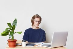 Serious male manager manages finances at home, uses laptop and calculator, looks at graphics with serious expression, drinks coffe royalty free stock images