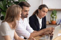Serious male mentor leader explain computer work to female employees stock images