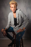 Serious male model wearing rugged jeans and sitting on a chair i. Portrait of serious male model wearing rugged jeans and sitting on a chair in studio while Royalty Free Stock Images