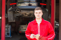 Serious male motor mechanic standing making notes. In front of a black sedan elevated on a hoist in a bay in a garage or workshop Royalty Free Stock Image