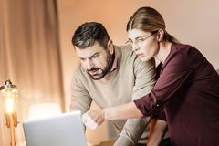 Serious male person looking at computer. Cannot understand. Pretty office worker wearing glasses and pointing at laptop while talking to her colleague Stock Photography