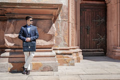 Serious male person waiting for somebody. Confident man wearing sunglasses is leaning against wall and holding case. He looking aside. Copy space on right side Royalty Free Stock Photos