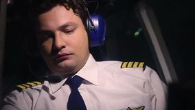 Serious male pilot in civil aviation uniform looking at flight control panel stock video