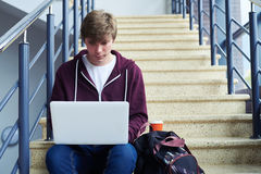 Serious male printing in laptop while sitting on stairs. Mid shot of serious male printing in laptop while sitting on stairs with copy space Royalty Free Stock Photography