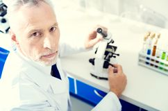 Serious male researcher working into camera. No time for mistake. Top view on a concentrated mature gentleman looking into the camera while sitting at a Stock Image