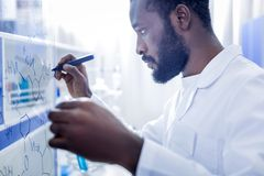 Serious male scientist writing a formula. Chemical chain. Serious nice male scientist holding a highlighter and looking at the whiteboard while writing a formula Royalty Free Stock Photos
