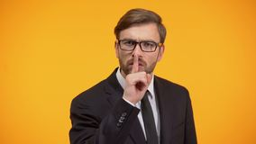 Serious male showing silence gesture, nondisclosure of personal data, secret. Stock footage stock video footage
