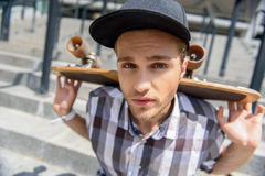Serious male skateboarder resting on stairs. Young man is holding skate on his shoulders. He is sitting on steps and looking at camera with seriousness Royalty Free Stock Photo