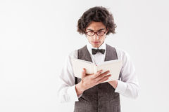 Serious male student is interested in literature. Confident young clever man is reading book with seriousness. He is standing in old-fashioned clothing. Isolated Royalty Free Stock Photography