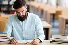 Serious male student reading book in the college library royalty free stock images