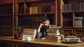 Serious male student reading a book in a library. Man with beard reading book on bookshelf background. Man in classic stock footage