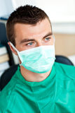 Serious male surgeon with mask and scrubs. Sitting in his office Stock Photo