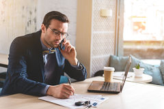 Serious male telling at cellphone in office Royalty Free Stock Photo
