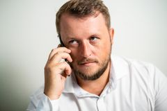 Serious male in a white shirt talking on the phone on a white gray background stock image