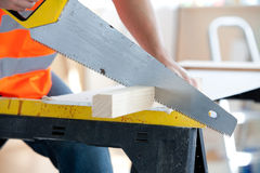 Serious male worker sawing a wooden board. Close-up of a serious male worker sawing a wooden board at work Royalty Free Stock Photos