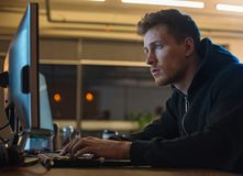 Serious male working with computer. Side view calm unshaven software specialist typing in digital device while locating at desk. Occupation concept Stock Images