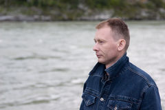 Serious man. Serious man in a jeans jacket with the lifted collar on coast of the mountain river Stock Photography