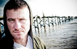 Serious Man. A man with an intense stare wearing a hooded sweatshirt with an old pier in the background Stock Images