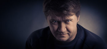 The serious man. The serious young man on a dark background royalty free stock images