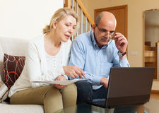 Serious man adn woman reading finance documents together. Serious men adn women reading finance documents together and using laptop in home interior royalty free stock photography