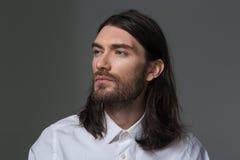 Serious man with beard and long hair looking away Royalty Free Stock Photos