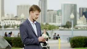 Serious man with a big amount of money on a street of Coronado. Young bearded businessman is counting his money while standing on a sidewalk stock footage
