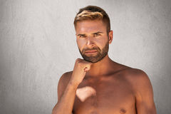 Serious man with bristle, dark attractive eyes, stylish hairdo standing topless while keeping his hand under chin isolated over gr stock photos