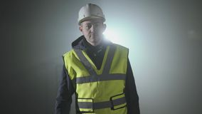Serious man in the builders uniform and helmet comes closer to the camera in front of black background with spotlight. Serious man in the builders uniform and stock video