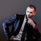 Serious man in a business suit, dark background, backlight blue and red tones Royalty Free Stock Image