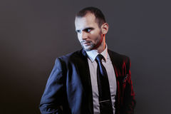 Serious man in a business suit, dark background, backlight blue and red tones Stock Photography