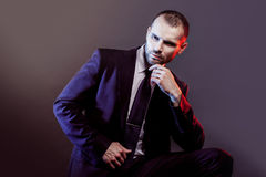 Serious man in a business suit, dark background, backlight blue and red tones Stock Images