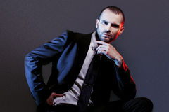 Serious man in a business suit, dark background, backlight blue and red tones Stock Photos
