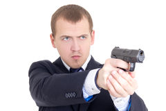Serious man in business suit shooting with gun isolated on white Stock Photo