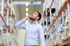 Serious man calling on smartphone at warehouse Royalty Free Stock Photography