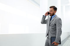 Serious man CEO having cell telephone conversation with clients. Young male economist is standing with touch pad in hand in modern office interior near copy Royalty Free Stock Photography
