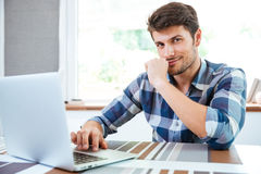 Serious man in checkered shirt working with laptop at home Royalty Free Stock Image