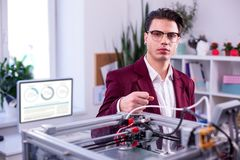 Serious man in clear glasses wearing dark red jacket and white shirt royalty free stock image