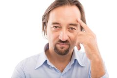 Serious man. Close-up portrait of serious middle-aged man pointing at his forehead Stock Photos