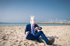 Serious man in comical mask sits on the sand and enjoys sunny day. Unusual guy in suit looking on wristwatch. Strange person relaxing on the beach Royalty Free Stock Photo